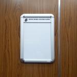 cartelera para 1 hoja carta instalada en ascensor de edificio