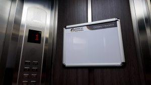 cartelera marco abatible doble carta personalizada instalada en ascensor