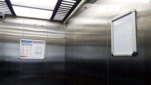 carteleras marco abatible instaladas en ascensor de clínica