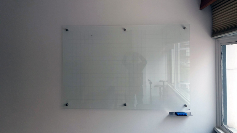 Tablero en vidrio templado con cuadrícula y portaborrador vista frente, tablero instalado en pared con 6 dilatadores, tablero con cuadricula, tablero borrable en vidrio,